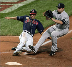 Grady Sizemore slides home on an eighth-inning wild pitch as New York Yankees hurler Joba Chamberlain tries to make the tag. The score tied Game 2 of the Indians-Yankees series 1-1 before Cleveland won it in the last of the 11th.