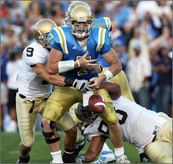 Notre Dame's Tom Zbikowski, left, and Trevor Laws force a fumble with their hit on UCLA quarterback Ben Olson.