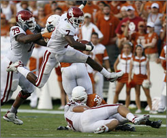 Oklahoma running back DeMarco Murray goes airborne over teammate Joe Jon Finley and Texas defender Scott Derry on his way to a 65-yard touchdown run in the third quarter.