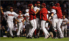 The Arizona Diamondbacks celebrate with closer Jose Velverde, center, after he recorded the final out of their 5-1 win against the Chicago Cubs during Game Three of the National League Divisional Series at Wrigley Field on in Chicago Saturday.