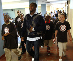 Braylon Edwards walks the halls of John Ford Rhodes High School with children that are part of his Advance 100 program which selects 100 eighth-graders through an essay competition and promises to provide a $10,000 gift toward college costs.