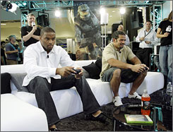 "Helping Microsoft promote its new Xbox game, Halo 3 (shown below), the Giants' Osi Umenyiora, left, and Kawika Mitchell try out the game at a store in Manhattan. Says Ravens tight end Todd Heap of players' delight in video games, ""It's kind of a release."""