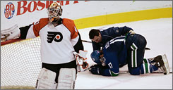 Ryan Kesler of the Canucks gets assistance from a trainer after being cross-checked by Philadelphia's Jesse Boulerice during Wednesday night's game in Vancouver. Flyers goalie Martin Biron is at left.