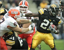 Iowa's Albert Young fends off Illinois linebacker J Leman to game some of his 99 yards.