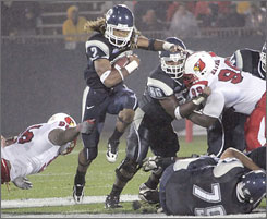 Connecticut's Andre Dixon, center, runs the ball against Louisville's Earl Heyman, right, and Daniel Cameron during their Big East battle outside Hartford.