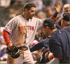 Mike Lowell celebrates scoring in the fifth inning. The World Series MVP later homered for the Red Sox, who completed a four-game sweep of the Colorado Rockies.