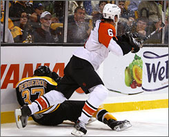 Patrice Bergeron is laid out by Philadelphia's Randy Jones during Saturday's game in Boston. The hit resulted in a two-game suspension for Jones. It also landed Bergeron in the hospital with a concussion and broken nose.