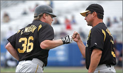 In this photo taken during spring training in 2003, then-Pirates third-base coach John Russell congratulates  Craig Wilson after a homer. Russell was named the Pirates' new manager on Monday.