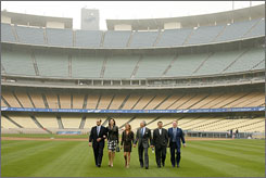 New manager Joe Torre walks with wife Ali walk to a centerfield platform at Dodger Stadium for an official announcement with team owners Jamie and Frank McCourt, general manager Ned Colletti and broadcaster Vin Scully.