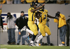Pat White, left, had company in the form of teammate Darius Reynaud during his 50-yard run for West Virginia's game-winning touchdown.