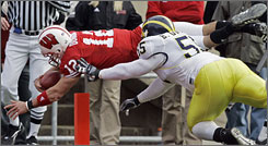 Tyler Donovan dives past Michigan's Brandon Graham for a Wisconsin touchdown.
