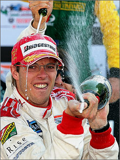 Champ Car driver Sebastien Bourdais sprays champagne on the podium after winning Sunday's Mexican Grand Prix in his last race on the tour before heading for Formula One.