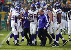 Minnesota's Adrian Peterson is helped off the field during the fourth quarter.