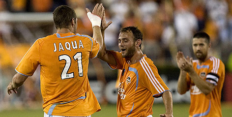 Houston forward Nate Jaqua gets congratulations from Brad Davis after scoring in the first half against Kansas City during their MLS playoff game last weekend.