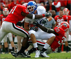 Georgia defenders Akeem Dent, left, and Rennie Curran put a big hit on Kentucky tight end Jacob Tamme.