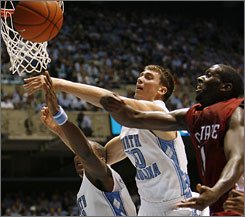 North Carolina's Tyler Hansbrough, center, and Deon Thompson, left, battle South Carolina State's David Cobb during the Tar Heels' romp Tuesday in Chapel Hill, N.C.