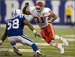 Kansas City running back Priest Holmes tries to avoid Indianapolis linebacker Gary Brackett during Sunday's game. Holmes has come back from injuries several times throughout his career. But the latest injury prompted Holmes to end his playing days.