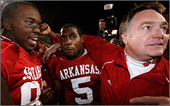 From left, Arkansas' Matterral Richardson, Darren McFadden and coach Houston Nutt celebrate defeating top-ranked Louisiana State in Baton Rouge. McFadden ran for 206 yards and three touchdowns in the Razorbacks' 50-48 triple-overtime win.