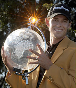 Aaron Baddeley of Australia holds the Australian Masters golf trophy aloft after beating Daniel Chopra of Sweden on the third playoff hole in Melbourne Sunday.