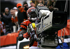 Chad Johnson took control of a TV camera to celebrate one of his three touchdowns in the Bengals' defeat of Tennessee.