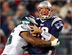 Philadelphia's Juqua Thomas sacks New England's Tom Brady during the first quarter. The Patriots survived a spirited effort from the Eagles to improve to 11-0.