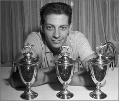 Bill Hartack, seen here posing with three of his five Kentucy Derby victory trophies, is one of only two riders to with five in his career.