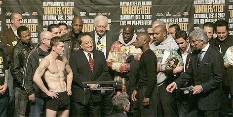 Ricky Hatton, left in black shorts, eyes WBC welterweight champion Floyd Mayweather Jr. during Friday's weigh-in in Las Vegas. The pair had to be separated during the festivities at which Mayweather weight the class limit 147 pounds, two more than Hatton.