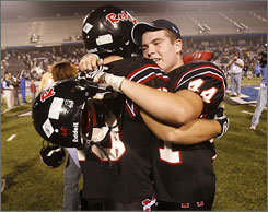 Maryville linebackers Luke Cox, right, and Jordan Halsne celebrate their state championship after the Rebels downed Maplewood 28-13.