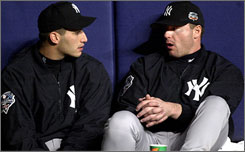 Andy Pettitte and Roger Clemens, both named on Thursday in George Mitchell's report on steroid use in baseball, chat during a World Series game in 2000. Pettitte has since admitted using human growth hormone in 2002.