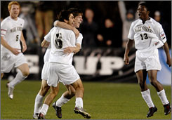 Wake Forest's Sam Cronin and Austin de Luz (6) hug as Mike Lahoud (13) joins the party after the Demon Deacons beat Ohio State 2-1 in the NCAA soccer final.