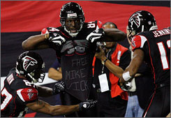 The Falcons' Roddy White, center, shows off his tribute to Michael Vick after scoring a touchdown against the Saints on Dec. 10. The NFL on Tuesday fined White  and four other Falcons  for that gestures and others like it.