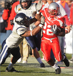 New Mexico running back Paul Baker tries to avoid the tackle of Nevada's Paul Pratt.