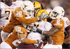 Texas gang tackles Dimitri Nance during the Holiday Bowl. The Longhorns won despite four fumbles by QB Colt McCoy and a wacky penalty on a Texas coaching aide.