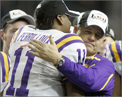 LSU quarterback Ryan Perrilloux hugs coach Les Miles after clinching the SEC crown.