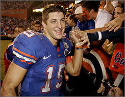 Florida quarterback Tim Tebow slaps hands with adoring fans after the Gators' victory over rival Florida State.
