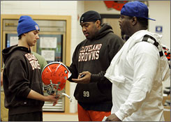 Cleveland Browns players Orpheus Roye and Robaire Smith sign a helmet for a locker room attendant while visiting the team's complext to clean out their lockers on Monday.