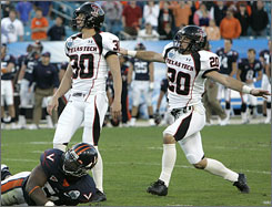 Texas Tech kicker Alex Trlica, center, holder Danny Amendola, right, and Virginia's Clint Sintim watch as Trlica's kick goes through the uprights to give the Red Raiders a 31-28 win.