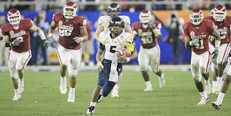 West Virginia's Pat White races for a first down against Oklahoma during the Fiesta Bowl. The Mountaineers won 48-28 as White ran for 150 yards and threw for 176 and two touchdowns.