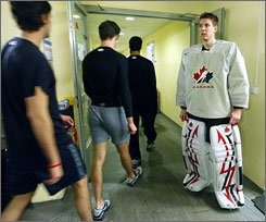 American hockey players file past Canadian goalie Steve Mason after practice on Jan. 1. The two teams face each other on Friday.