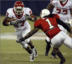 Rutgers running back Ray Rice tries to find room against the defense of Ball State's Eddie Burke.