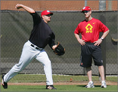 "Roger Clemens, left, works with former trainer Brian McNamee in February 2006. McNamee says he injected Clemens with illegal performance-enhancing drugs, allegations Clemens said in a 60 Minutes interview on Sunday are ""completely false."""