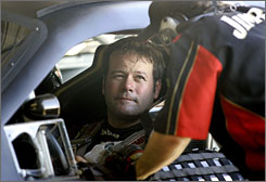 Robby Gordon confers with a crewmember during a break in testing at Daytona. Gordon was 38th-fastest out of 45 drivers in Monday's afternoon session.