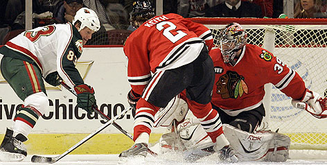 Matt Foy scores on Chicago's Nikolai Khabibulin as Duncan Keith tries to defend. Minnesota needed only 16 shots to net five goals in beating the slumping Blackhawks.