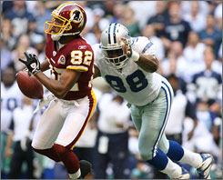 Cowboys outside linebacker Greg Ellis chases down the Redskins'  Antwaan Randle El during their matchup in Dallas. With 12 sacks in 2007, Ellis was awarded the AP's NFL comeback player of the year award.