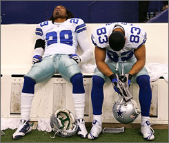 Dejected Dallas players Keith Davis, left, and Terry Glenn sit on the bench in the closing minutes of the Cowboys' loss.