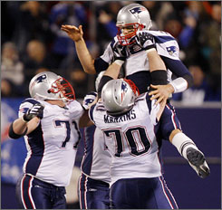 Patriots offensive linemen Logan Mankins, right, and Russ Hochstein hoist quarterback Tom Brady after his record-setting 50th touchdown pass on Dec. 29.