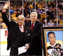 Former Bruins player Willie O'Ree acknowledges the cheeers from the crowd in Boston after being honored on the 50th anniversary of breaking the color barrier in the NHL. Looking on is Bruins legend John Bucyk.