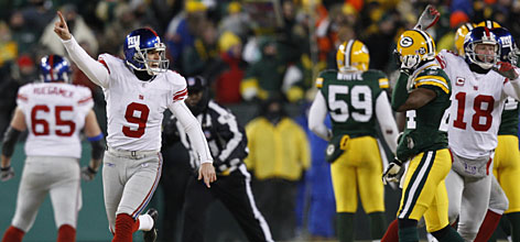 "Giants kicker Lawrence Tynes, left, celebrates his 47-yard game-winning field goal in overtime that clinched a Super Bowl berth. Said wide receiver Plaxico Burress of defeating the Packers, ""It doesn't seem real right now."""