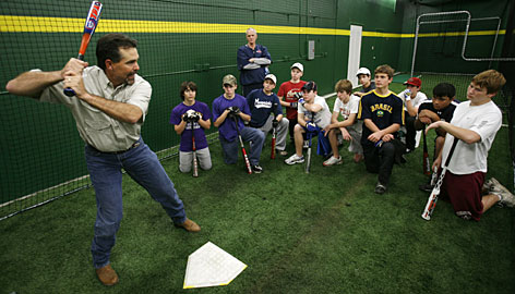 Trey Hillman demonstrates proper batting techniques to a group of teenagers, including his son T.J., at a baseball center in Austin.
