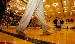 IUPUI coach Ron Hunter walks barefoot onto the court for Thursday night's game against Oakland in support of a drive for shoe donations.